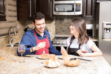 Happy couple having meal together in kitchen
