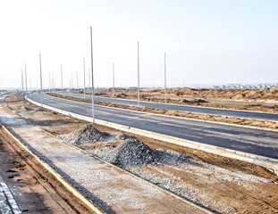 Under construction road in the city with lighting poles