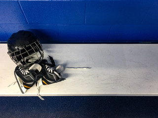 Top view of kid hockey skates and helmet in white bench in locker room with copy space