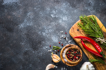 Olive oil, herbs and spices on a dark stone table.