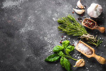 Spices and herbs over black stone table.