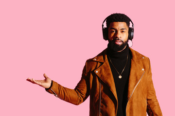 Portrait of a cool man with beard and headphones gesturing with his hand out isolated on pink studio background