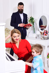 Child stand near piano keyboard, white interior background. Mother teaches kid play piano, musical instrument. Boy adorable try to play piano, while parents watching him. Musician education concept.