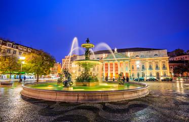Night scene in Rossio square, illuminated architecture of the fountain and National theatre of Maria, in Lisbon - Portugal