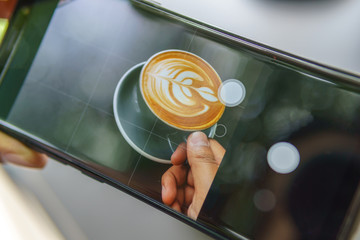 close up of smartphone taking photo of hand holding cup of latte art coffee.