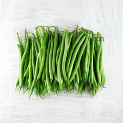fresh green beans on white wooden kitchen plate, shabby chic, can be used as background