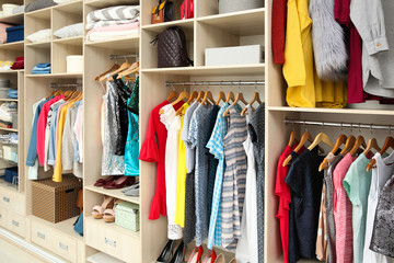 Large wardrobe with female clothes and accessories in dressing room