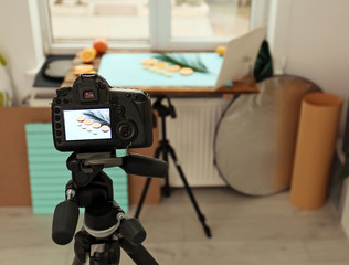 Professional camera with picture of cut fruits and palm leaf on display in studio. Food photography