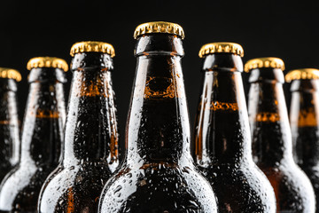 Glass bottles of beer on black background, closeup