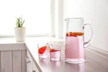Jug and glasses of fresh lemonade with grapefruit on table