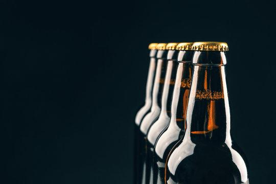 Glass bottles of beer on black background