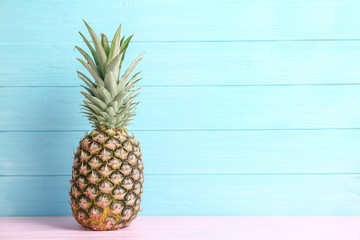 Fresh pineapple on table against color wall