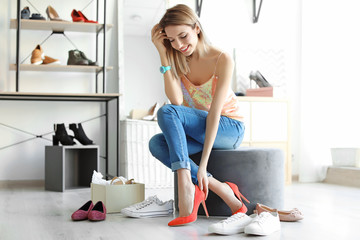 Young woman trying on shoes in store Wall mural