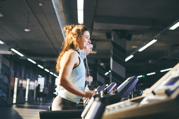 beautiful young woman with lush curly hair in vest and leggings runs in the gym on treadmill, cardio training machine and weight loss. On head big white headphones, listening music. Sunny weather
