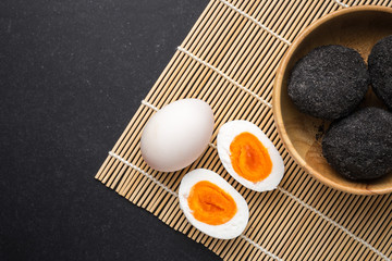 Thai style black and white salted egg in wooden bowl on black stone background