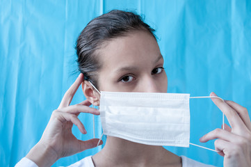 A girl doctor dresses a mask on a blue background