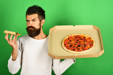 Pizza. Handsome sexy bearded man with serious face eating pizza. Man eating pizza and holds box. Hipster with long beard and mustache in white pullover eats fast food. Not helpful food.