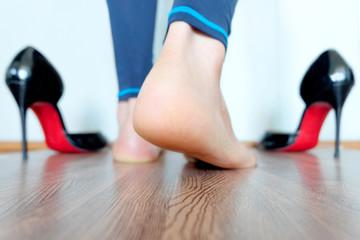 Heels beautiful woman's heel lift Black high-heeled shoes background on wooden floor