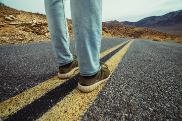 Man ready to take a new way and make a step to new life concept. Feet on empty and free aspalt road in desert.