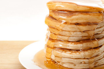 American pancake for breakfast, sweet snack and high calorie dessert concept with close up on flowing honey or maple syrup on a stack of thick pancakes isolated on white  background with copy space