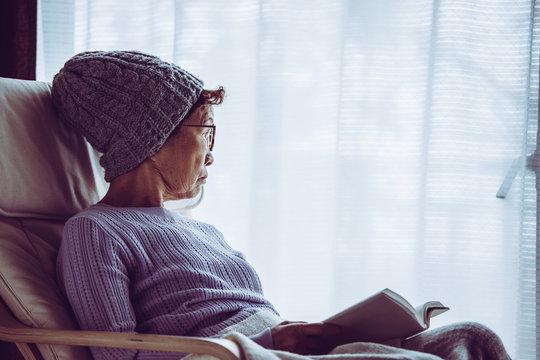 窓際の椅子に座って本を読むシニア女性