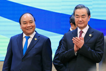 Vietnam's PM Nguyen Xuan Phuc and Chinese FM and State Councilor Wang Yi smile during a group photo at the Mekong Greater Sub-Region Summit in Hanoi