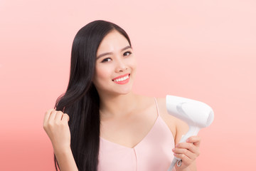 Portrait of beautiful asian woman drying her long hair with dryer