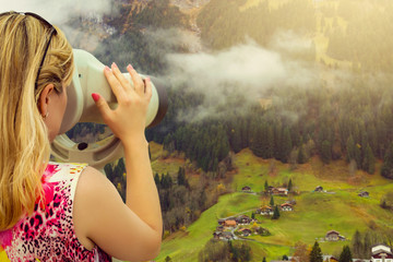Young girl looking through a coin operated binoculars switzerland