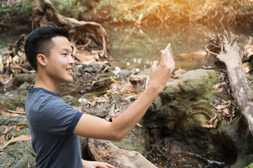 Selfie photo concept : Asian young man holding smartphone for selfies at  forest, beautiful scenery for peachful in spring , It shows moisture, tranquility and refreshing of rainforest in Thailand