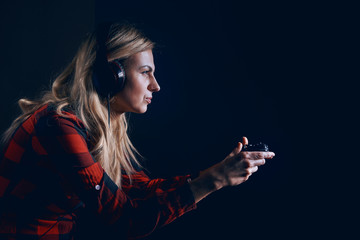 girl gamer in headphones and with a joystick enthusiastically playing on the console