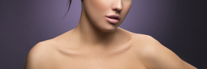 Lips and shoulders of model girl with natural make-up and clean skin. Part of woman face. Facial treatment concept