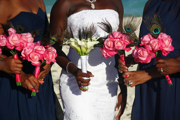 African American bride on white dress together with bridesmaids holding colorful flower bouquets on wedding day outdoors. Glamorous ceremony event closeup. Happiness concept