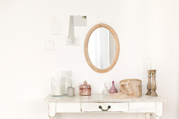 White colored vintage table and mirror hanging on the wall.