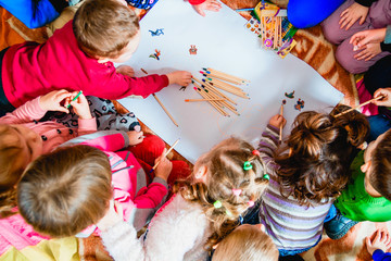 several small children draw on a sheet of paper with pencils. A view from above.