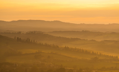 Sunrise in the lands of Tuscany. Warm colors on the hills and haze
