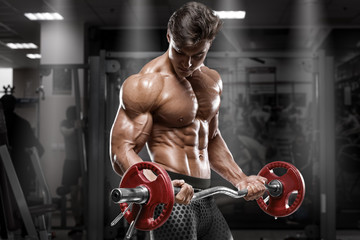 Muscular man working out in gym doing exercises, strong bodybuilder, abs Wall mural