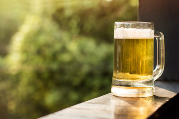 Drinking Beer in Summer Concept. Glass of Beer on Balcony. Natural Sunlight and Tree as background, Warm Tone