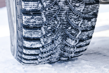 The car tire in the snow close up. Car tracks on the snow. Traces of the car in the snow. Winter tires. Tyres covered with snow at winter road