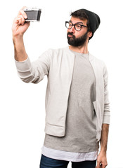 Hipster man holding a camera on white background