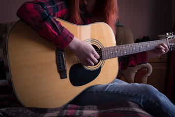 young girl playing the guitar. close-up