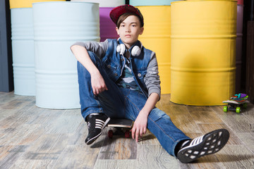 Stylish teen boy wearing jeans with a skateboard  on a colorful background. Concept lifestyle and sportive life.