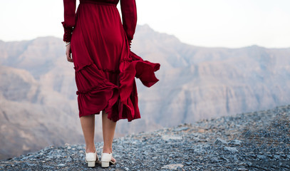 Fashionable girl in red dress on a desert mountain top