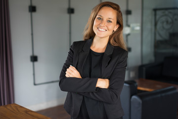 Closeup portrait of smiling young beautiful brown-haired woman looking at camera and standing with her arms crossed in hotel lounge. Successful business woman concept. Front view.