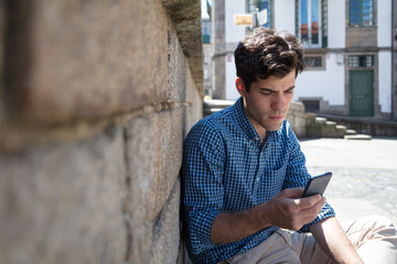 Portrait of young business man looking at his smartphone