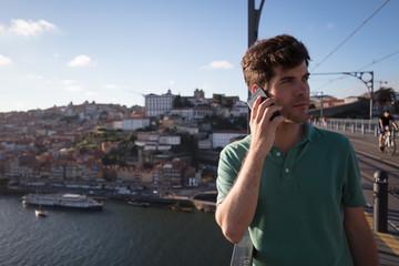 Man calling with phone on bridge in Porto, Portugal
