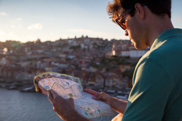Man looking at tourist map at sunset in Porto, Portugal