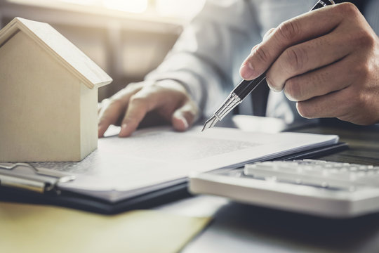 Businessman or lawyer accountant working financial investment on office, using calculator analysis finance document report real estate and home loan insurance