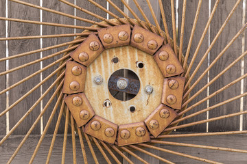 Old Hay Rake Wheel on a wooden fence.