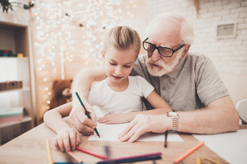 Grandfather, grandson and granddaughter at home. Grandpa is helping children draw.