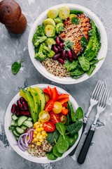 Healthy lunch Buddha bowls. Avocado, quinoa, red beans, spinach, avocado and fresh vegetables and with grilled chicken and grilled vegetables.